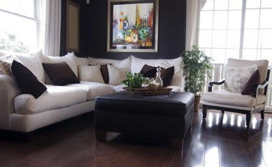 New Uses living room with dark wood floor, white couch with dark-grey pillows, dark curtains, white and wood side chair, dark wood coffee table