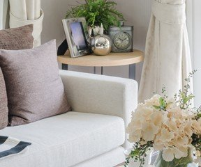 New Uses living room white couch with neutral pillows, vase with white flowers on coffee table, side table with frames and vase in background, window with white curtains