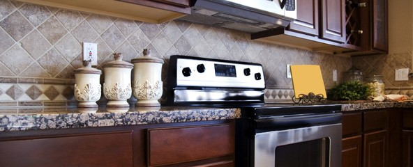 New Uses kitchen with dark-brown cabinetry and stainless steel appliances, neutral backsplash tile and cream-color canisters on multicolor countertop