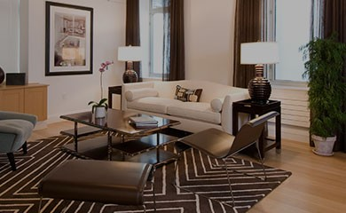 New Uses living room with white couch and grey side chair and tan sideboard, white walls and artwork in black frames on walls, glass-top coffee table, graphic brown rug