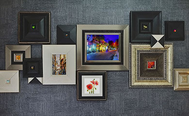 wall gallery of artwork, silver and black frames with colorful photos and paintings inside