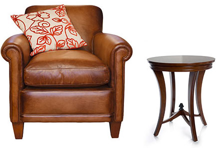 New Uses tan leather chair with graphic white and orange pillow, small dark wood side table against white background