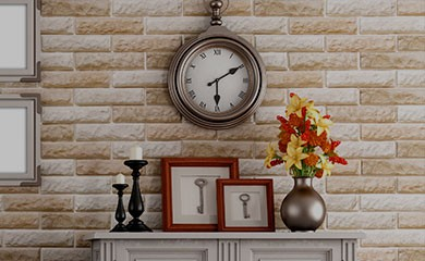New Uses home with brick wall with two artwork frames and clock handing on wall, fireplace mantel with two black candlesticks and two red frames and small metallic vase with red and yellow flowers sitting on mantel