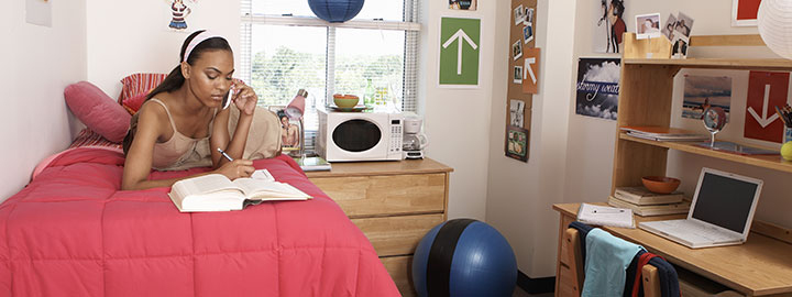 New Uses model in dorm room doing her homework on a bed with desk and microwave and exercise ball in the room as well