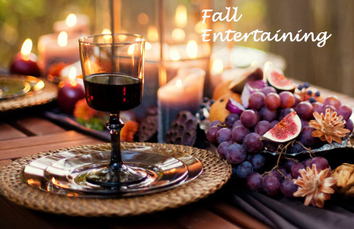 New Uses table setting outdoors with candles and glass plates, placemats, wine glass, grapes and fig and text that says fall entertaining