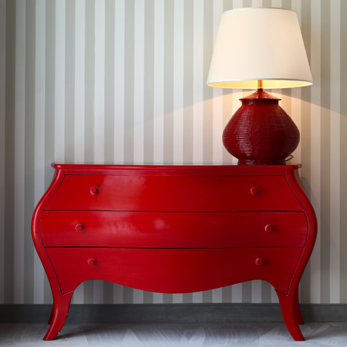 New Uses bright-red painted dresser with rounded sides and three large drawers, red lamp sitting on top of dresser and tan- and white-striped wallpaper in the background