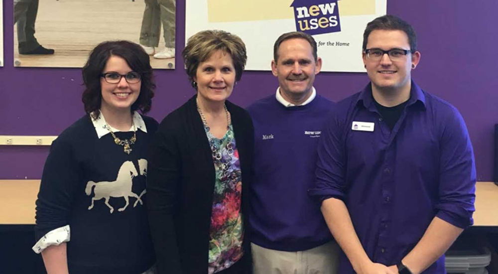 Franchisee Mark Hoon and family standing in a New Uses store with purple walls